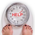 47859160 - low section of woman on weight scale with help text over white background